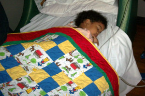 Child with one of Quilts For Kids donated quilts.